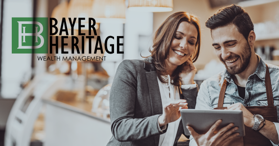 Bayer Heritage Wealth Management logo on image of woman helping small business owner in bakery.